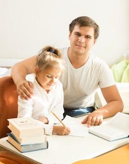 Portret przystojny mężczyzna pomaga córce w odrabianiu prac domowych