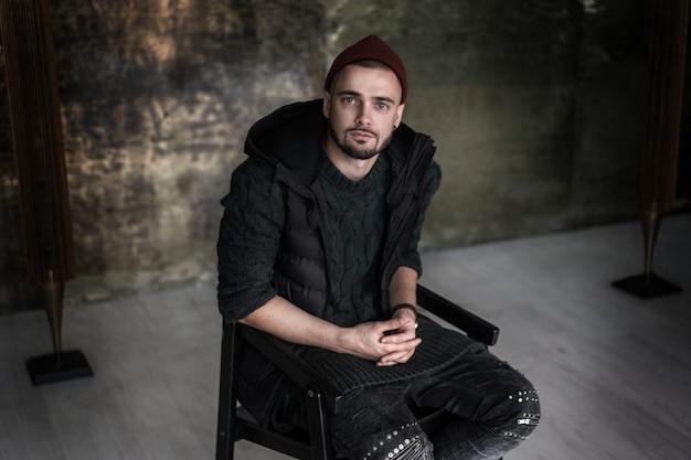 Portret przystojny mężczyzna siedzi wygodnie w trend loft