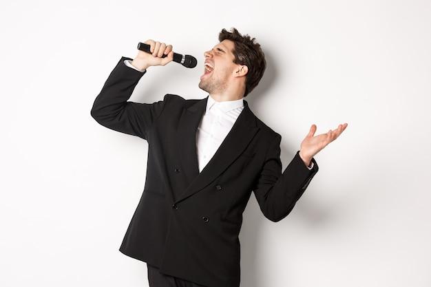 Portret przystojny mężczyzna śpiewa piosenkę z pasją, stojąc w czarnym garniturze, trzymając mikrofon i wykonując, pozowanie na białym tle.