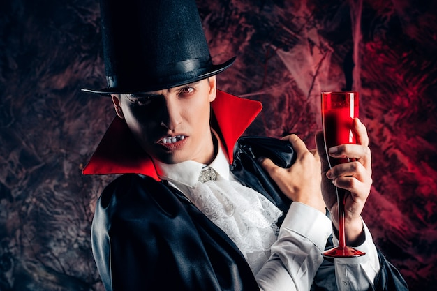 Portret przystojny mężczyzna ubrany w kostium drakuli na halloween. wampir trzyma szklankę krwi
