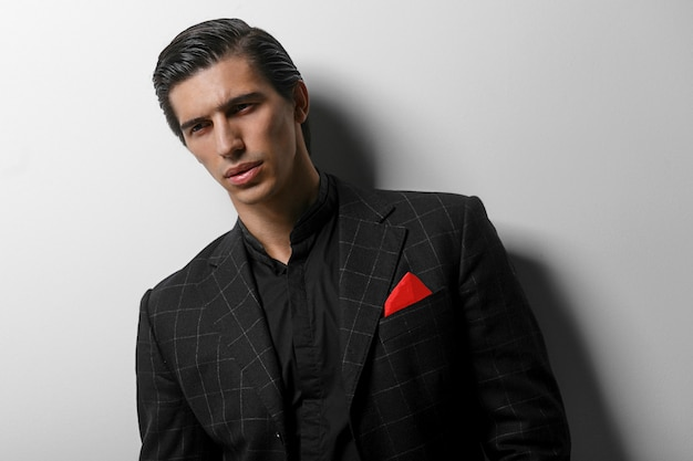 Portret przystojny mężczyzna w czarnym garniturze z czerwonym jedwabnym szalikiem w kieszeni, na białym tle.