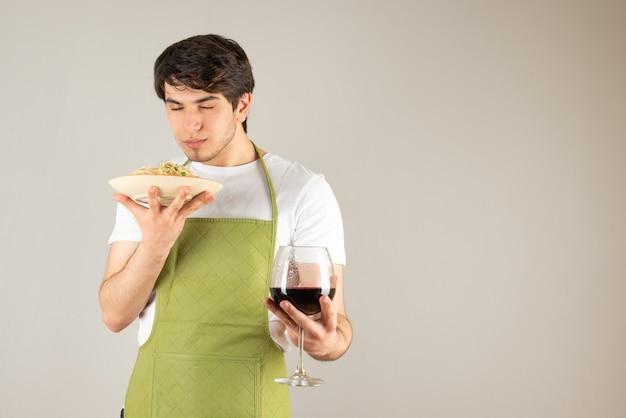 Portret przystojny mężczyzna w fartuchu trzyma talerz z makaronem i kieliszek wina.