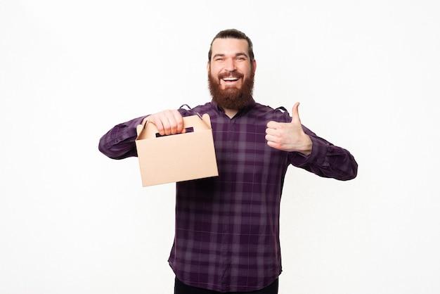 Portret przystojny mężczyzna w kraciastej koszuli, trzymając pudełko na lunch i pokazując kciuk do góry