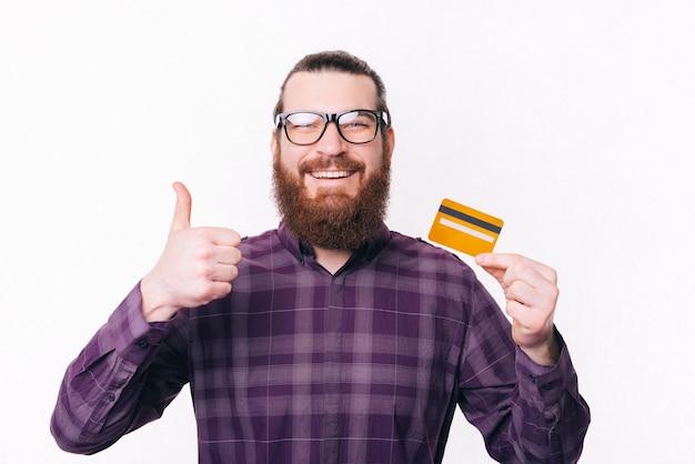 Portret przystojny mężczyzna w okularach, trzymając kartę kredytową i pokazując kciuk do góry
