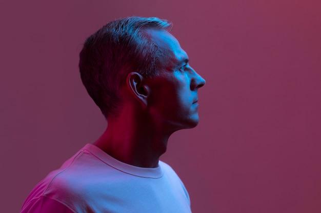 Portret przystojny mężczyzna w średnim wieku w neonowych światłach