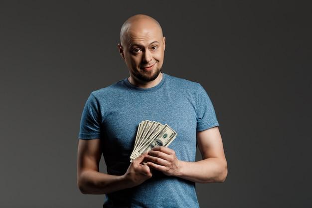 Portret przystojny mężczyzna w szarej koszuli gospodarstwa pieniądze na ciemnej ścianie