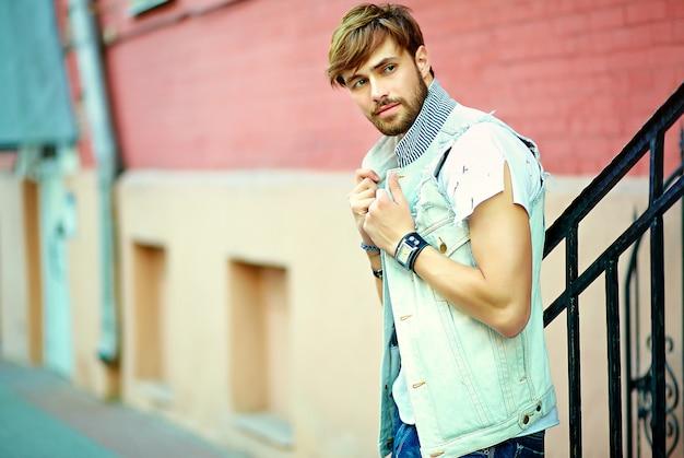 Portret przystojny mężczyzna w ubrania stylowe hipster. atrakcyjny facet pozuje na ulicy