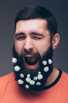 Portret przystojny mężczyzna z brodą kwiatów na białym tle na szarej ścianie