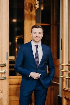Portret przystojny mężczyzna z zarostem, ubrany w oficjalny garnitur, ma pozytywny wyraz