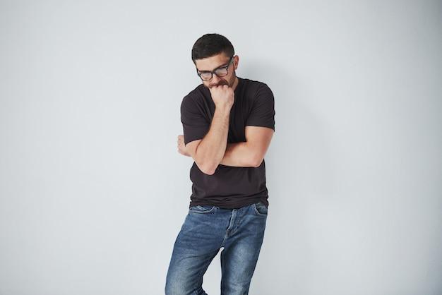 Portret przystojny młodego człowieka główkowanie na coś, odizolowywający na bielu