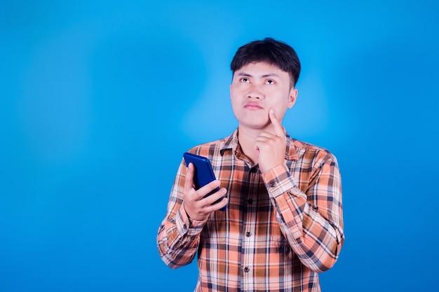 Portret przystojny młody azjatycki mężczyzna nosić pasiastą koszulęmyślenie na niebieskim tle