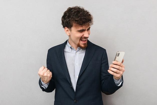 Portret przystojny młody biznesmen na białym tle nad szarą ścianą zrobić gest zwycięzcy za pomocą telefonu komórkowego.