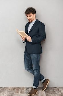 Portret przystojny młody biznesmen na białym tle nad szarej ścianie czytania książki.