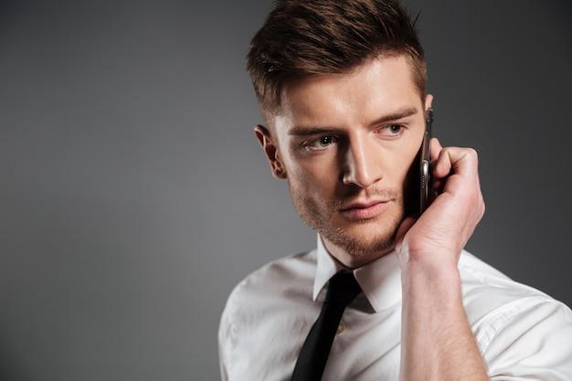 Portret przystojny młody biznesmen rozmawia przez telefon komórkowy