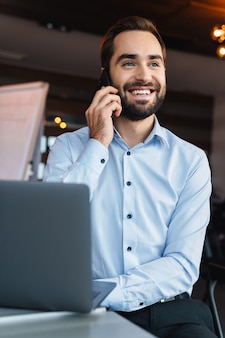 Portret przystojny młody biznesmen ubrany w białą koszulę, rozmawiający na telefonie komórkowym i korzystający z laptopa podczas pracy w biurze