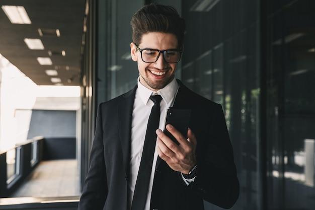 Portret przystojny młody biznesmen ubrany w formalny garnitur stojący na zewnątrz budynku ze szkła i trzymając telefon komórkowy