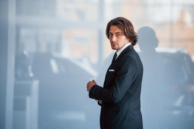 Portret przystojny młody biznesmen w czarnym garniturze i krawat.