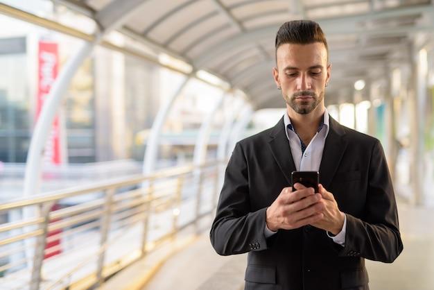 Portret przystojny młody biznesmen włoski na zewnątrz w mieście na sobie garnitur