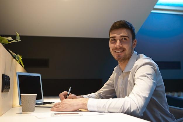 Portret przystojny młody biznesmen z zarostem patrząc z satysfakcjonującym uśmiechem