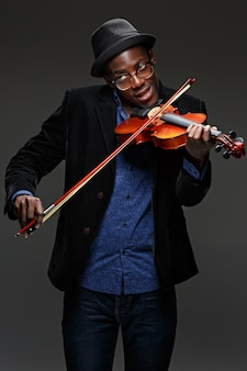 Portret przystojny młody czarny uśmiechnięty mężczyzna w kapeluszu gra na skrzypcach w ciemności