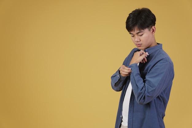 Portret przystojny młody człowiek azjatycki w odzieży casual zapinanie rękawów mankiet koszuli