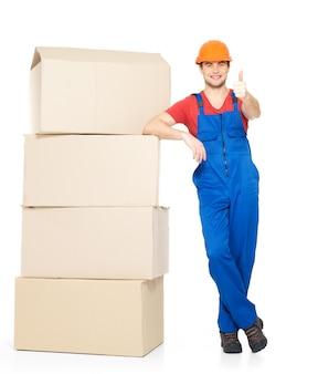 Portret przystojny młody człowiek dostawy z papierowymi pudełkami przedstawiający kciuki do góry znak na białym tle
