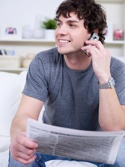 Portret przystojny młody człowiek mówi przez telefon i trzymając gazetę
