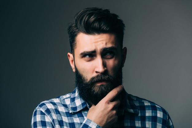 Portret przystojny młody człowiek myśli na białym tle na szarej ścianie