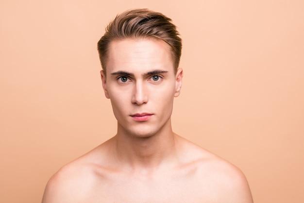 Portret przystojny młody człowiek na białym tle na pastelowy beż
