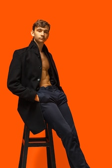 Portret przystojny młody człowiek na pomarańczowej ścianie