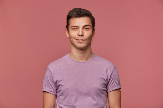 Portret przystojny młody człowiek nosi w pustej koszulce, patrzy w kamerę z uśmiechem i radosną miną, stoi na różowym tle.