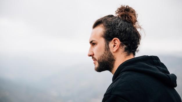 Portret przystojny, młody człowiek, patrząc od hotelu