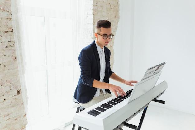 Portret przystojny młody człowiek patrzeje muzyka prześcieradło bawić się pianino