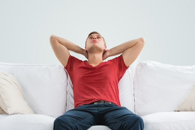 Portret przystojny młody człowiek patrzeje upwards podczas gdy relaksujący i marzący w domu