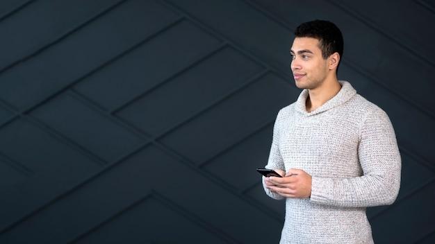 Portret przystojny młody człowiek trzyma jego telefon
