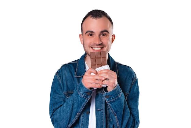 Portret przystojny młody człowiek trzyma pasek czekolady