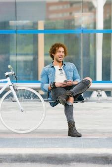 Portret przystojny młody człowiek uśmiechający się, gdy używa swojego telefonu komórkowego na ulicy.