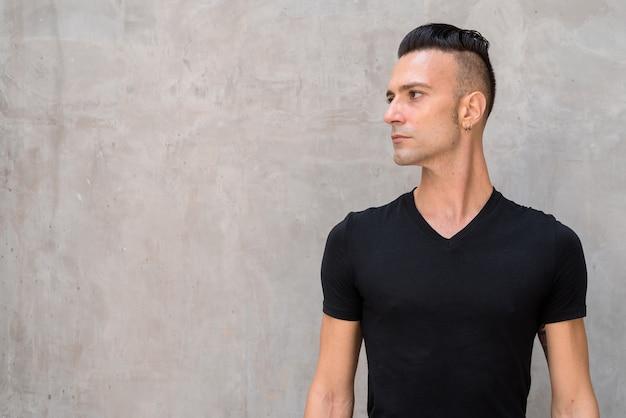 Portret przystojny młody człowiek z podcięciem na sobie czarną koszulkę i myślenie