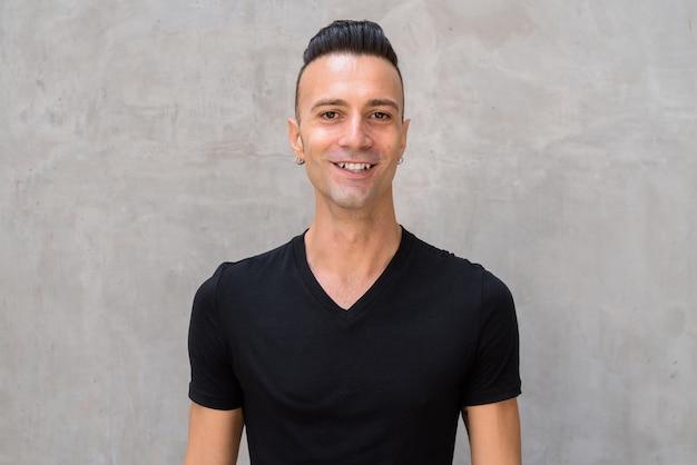 Portret przystojny młody człowiek z podcięciem na sobie czarną koszulkę i uśmiechnięty