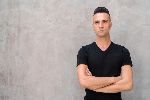 Portret przystojny młody człowiek z podcięciem na sobie czarną koszulkę podczas myślenia