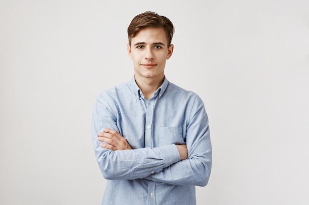 Portret przystojny młody człowiek z skrzyżowanymi rękami