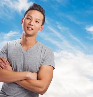 Portret przystojny młody mężczyzna azjatyckich z niebem w tle