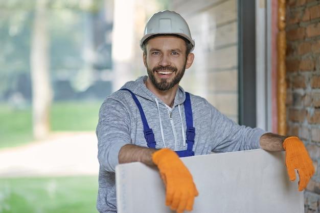 Portret przystojny młody mężczyzna budowniczy w twardym kapeluszu, patrząc pozytywnie trzymając płytę gipsowo-kartonową podczas pracy