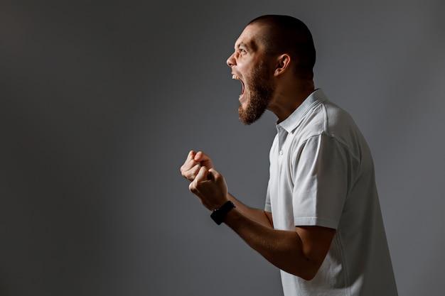 Portret przystojny młody mężczyzna krzyczy, zdenerwowany na szaro