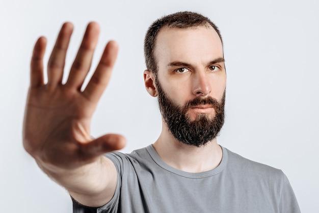 Portret przystojny młody mężczyzna marszcząc brwi, patrząc na aparat trzymając rękę naprzeciwko i mówiąc gest stop na białej ścianie