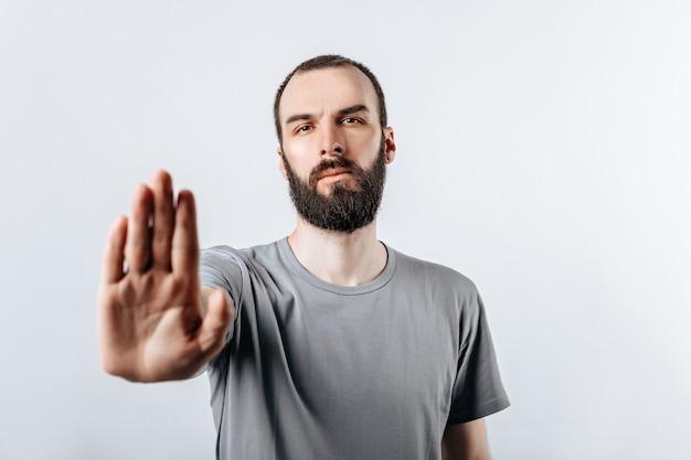 Portret przystojny młody mężczyzna marszcząc brwi patrząc na kamerę trzymającą rękę naprzeciwko i mówiący gest stop na białym tle z miejscem na reklamę makiety