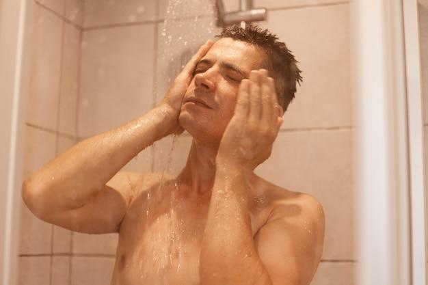 Portret przystojny młody mężczyzna pod prysznicem, stojąc pod gorącą wodą, myjąc twarz, pozowanie nago, trzymając zamknięte oczy, odświeżenie po ciężkim dniu pracy.