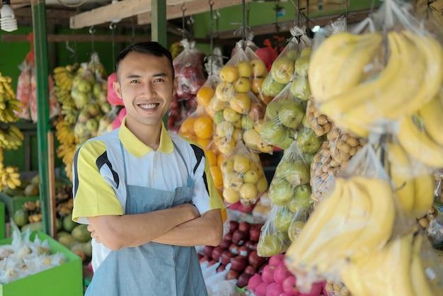 Portret przystojny młody mężczyzna pracujący w sklepie z owocami w pasie