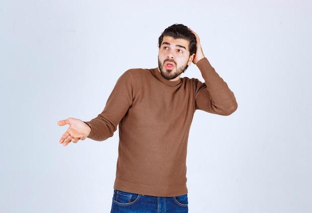 Portret przystojny młody mężczyzna trzyma głowę i pokazuje rękę.