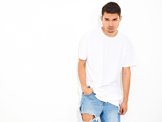 Portret przystojny młody model mężczyzna ubrany w ubrania dżinsy i pozowanie t-shirt. skrzyżowane ręce